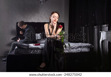 Young Couple Having Misunderstanding While Sitting at the Bedroom - stock photo