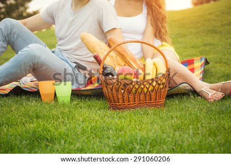 Young couple having picnic in the park. Man and woman came with basket full of food and drinks. - stock photo