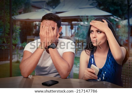 Young Couple Having Problems with Their Smart Phones - Young adult couple with smart phones upset out on a date