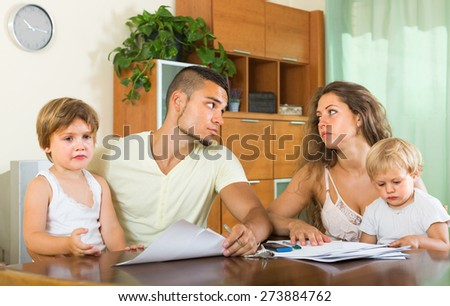 Young couple having quarrel in front of children at home. Focus on man - stock photo
