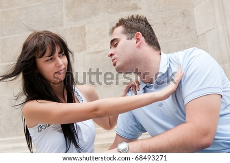 Young couple having relationship problems - woman refuses kissing from man - stock photo