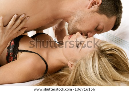 Young couple having sex in bed, kissing.
