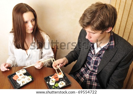Young couple having supper after hard day at their apartment - stock photo
