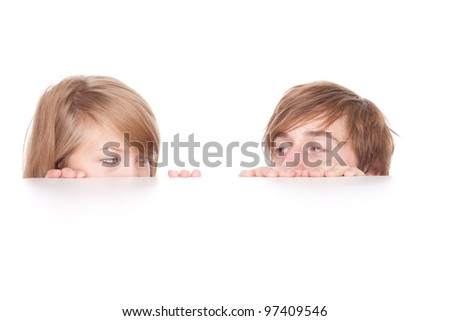 young couple hiding behind and peeking behind the white table - stock photo