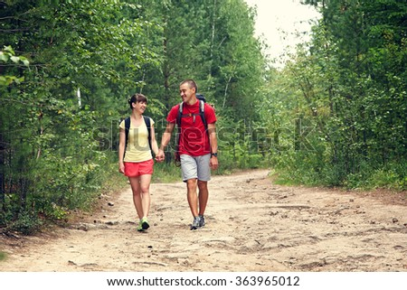 Young couple hikers in forest. sports man and woman with backpacks in the hike in nature