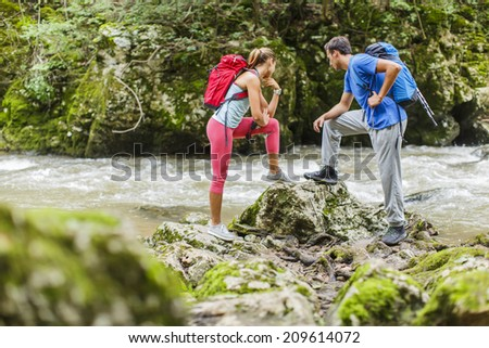 Young couple hiking by the river - stock photo