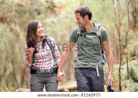 Young couple hiking in forest looking happy. Man and woman hikers holding hands walking in nature. From Aguamansa, Tenerife, Spain - stock photo