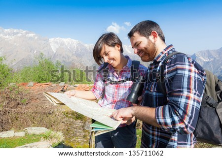 Young Couple Hiking Looking at Map - stock photo