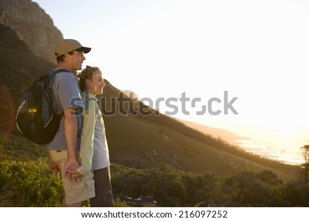 Young couple hiking, looking at view, side view (lens flare) - stock photo