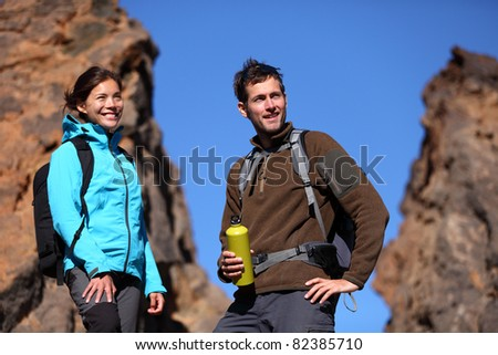 Young couple hiking. Outdoors hikers portrait mountain scenery. Asian woman and Caucasian man.