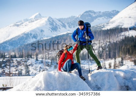 Young couple hiking outside in sunny winter mountains - stock photo