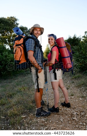 young couple hiking together with backpack on an adventure trek - stock photo