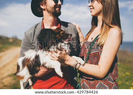 young couple hipster in love walking with dog in countrysidea - stock photo