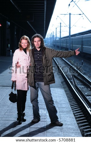Young couple hitchhiking at train station - stock photo