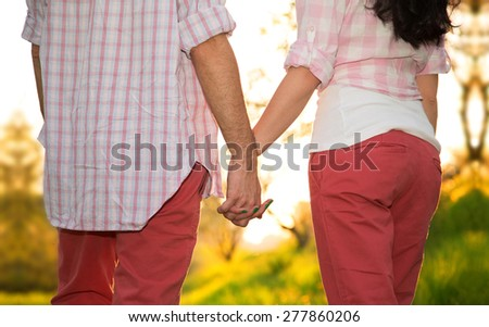 Young couple hold each other's hands summer on sunny park background. Concept shoot of friendship and love of man and woman. Two hands over sun ray and nature. Young couple in Love Story on nature. - stock photo