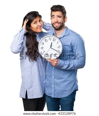 young couple holding a clock - stock photo