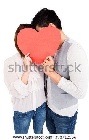 Young couple holding a heart shape on white background