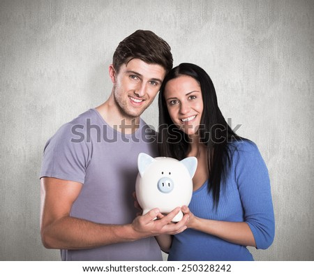 Young couple holding a piggy bank against weathered surface - stock photo