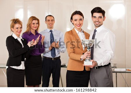young couple holding a trophy; happy business people celebrating their victory, applauded by their partners - stock photo