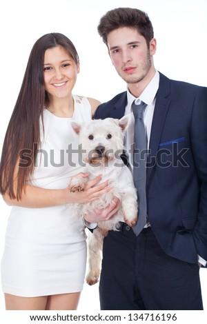 young couple holding a white dog - stock photo