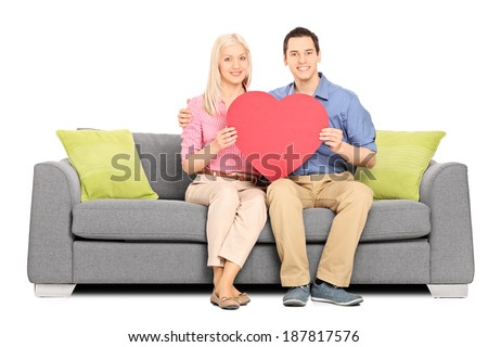 Young couple holding big red heart seated on sofa isolated on white background - stock photo