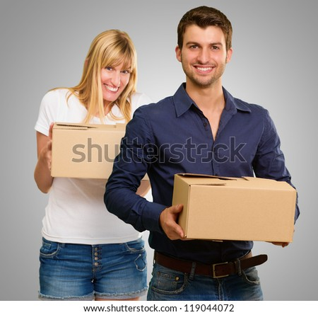 Young Couple Holding Cardboard Box On Gray Background - stock photo