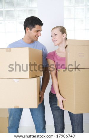 Young couple holding cardboard boxes. They're smiling and looking at each other's. Front view. - stock photo