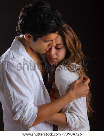 Young couple holding each other on black background - stock photo
