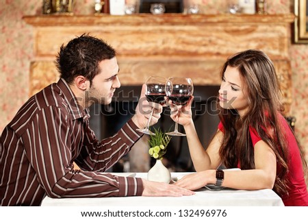 Young couple holding glasses of wine and cheers