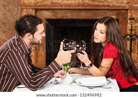 Young couple holding glasses of wine and cheers - stock photo