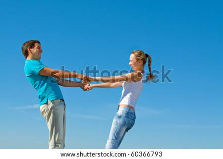 young couple holding hands against blue sky - stock photo