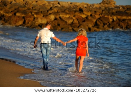 Young couple holding hands at beach enjoying romance at sun. Young happy couple in love on romantic summer holidays vacation. Young lovers in casual clothing. Asia woman, Caucasian man. - stock photo