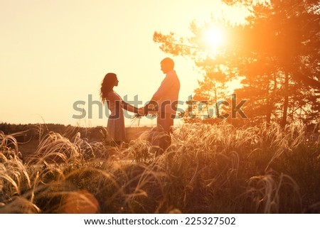 Young couple holding hands at sunrise - stock photo