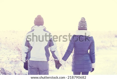 Young couple holding hands in a winter field - stock photo