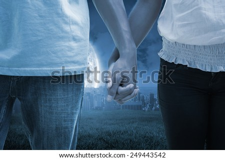 Young couple holding hands in the park against large moon over city - stock photo