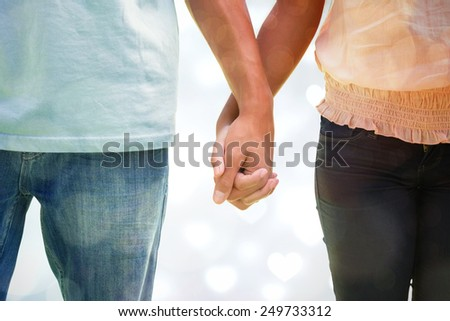Young couple holding hands in the park against valentines heart design