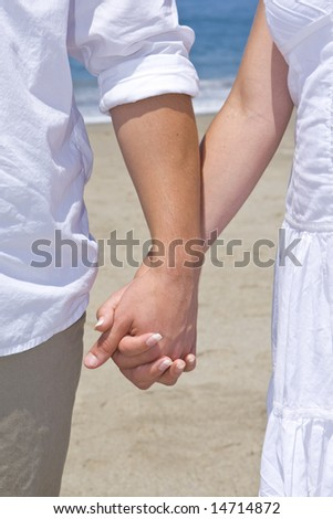 Young couple holding hands on the beach - stock photo