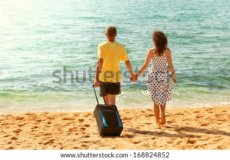 Young couple holding hands staying on the beach back to camera and looking on the sea - stock photo
