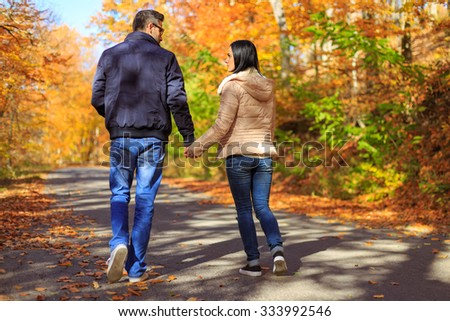 Young couple holding hands while taking a walk in nature - stock photo