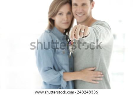 Young couple holding keys - selective focus on keys - stock photo