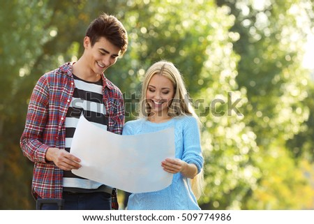 Young couple holding map in the park