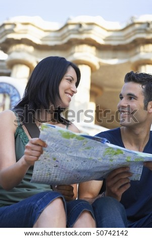 Young couple holding map, portrait - stock photo