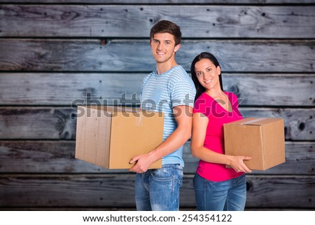 Young couple holding moving boxes against grey wooden planks - stock photo