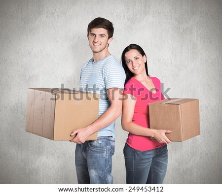 Young couple holding moving boxes against weathered surface - stock photo