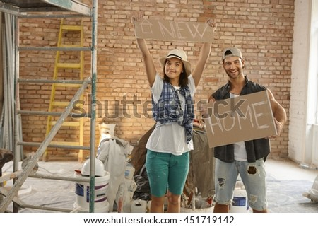 Young couple holding new home text at renovation site. - stock photo