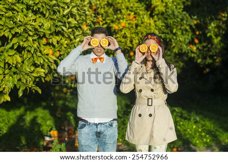 young couple holding oranges over eyes. - stock photo