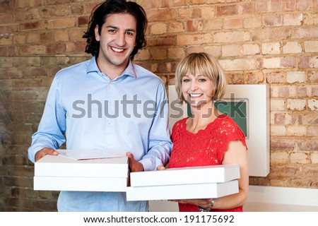 Young couple holding packed pizza boxes - stock photo