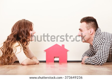 Young couple holding paper house and key. Husband and wife dreaming about new home. Housing and real estate concept. - stock photo