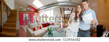 Young couple holding the keys and ownership document on their new apartment - stock photo