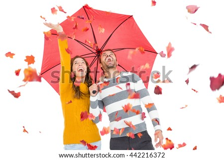 Young couple holding umbrella and playing with maple leaves on white background - stock photo